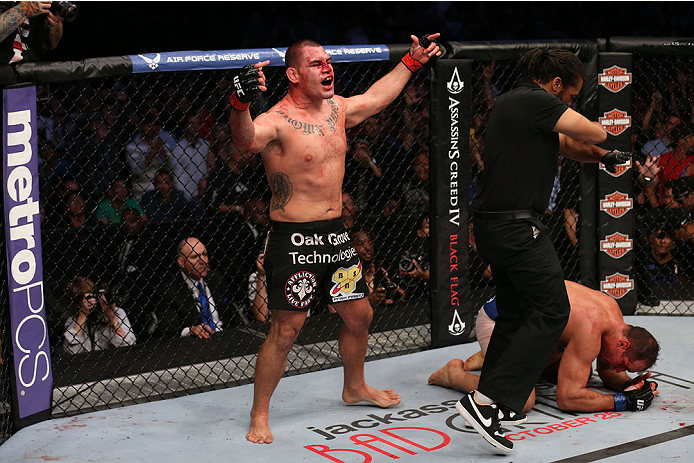 HOUSTON, TEXAS - OCTOBER 19:  Cain Velasquez (black shorts) celebrates after defeating Junior Dos Santos by TKO after referee Herb Dean calls a stop to the fight in their UFC heavyweight championship bout at the Toyota Center on October 19, 2013 in Houston, Texas. (Photo by Nick Laham/Zuffa LLC/Zuffa LLC via Getty Images)