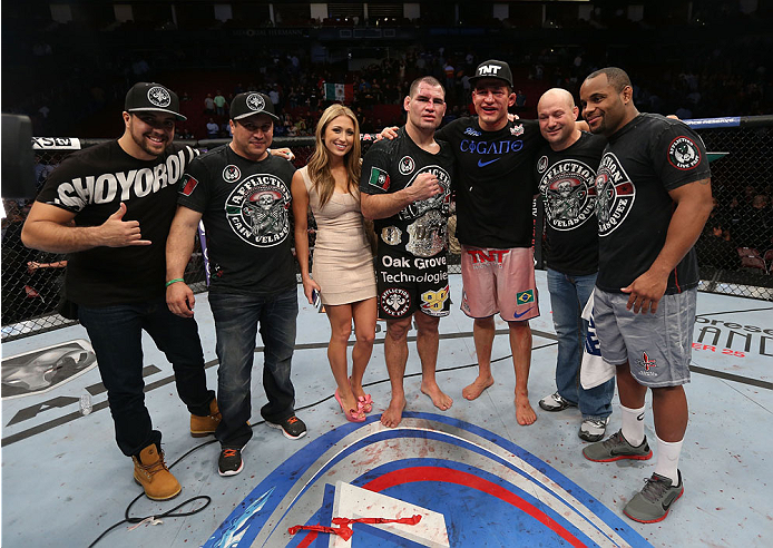 HOUSTON, TEXAS - OCTOBER 19:  Cain Velasquez (C)  and his wife Michelle celebrate with his corner, Daniel Cormier (R)  and Junior Dos Santos (3rd from right) while retaining the UFC heavyweight championship belt in their UFC heavyweight championship bout at the Toyota Center on October 19, 2013 in Houston, Texas. (Photo by Nick Laham/Zuffa LLC/Zuffa LLC via Getty Images)