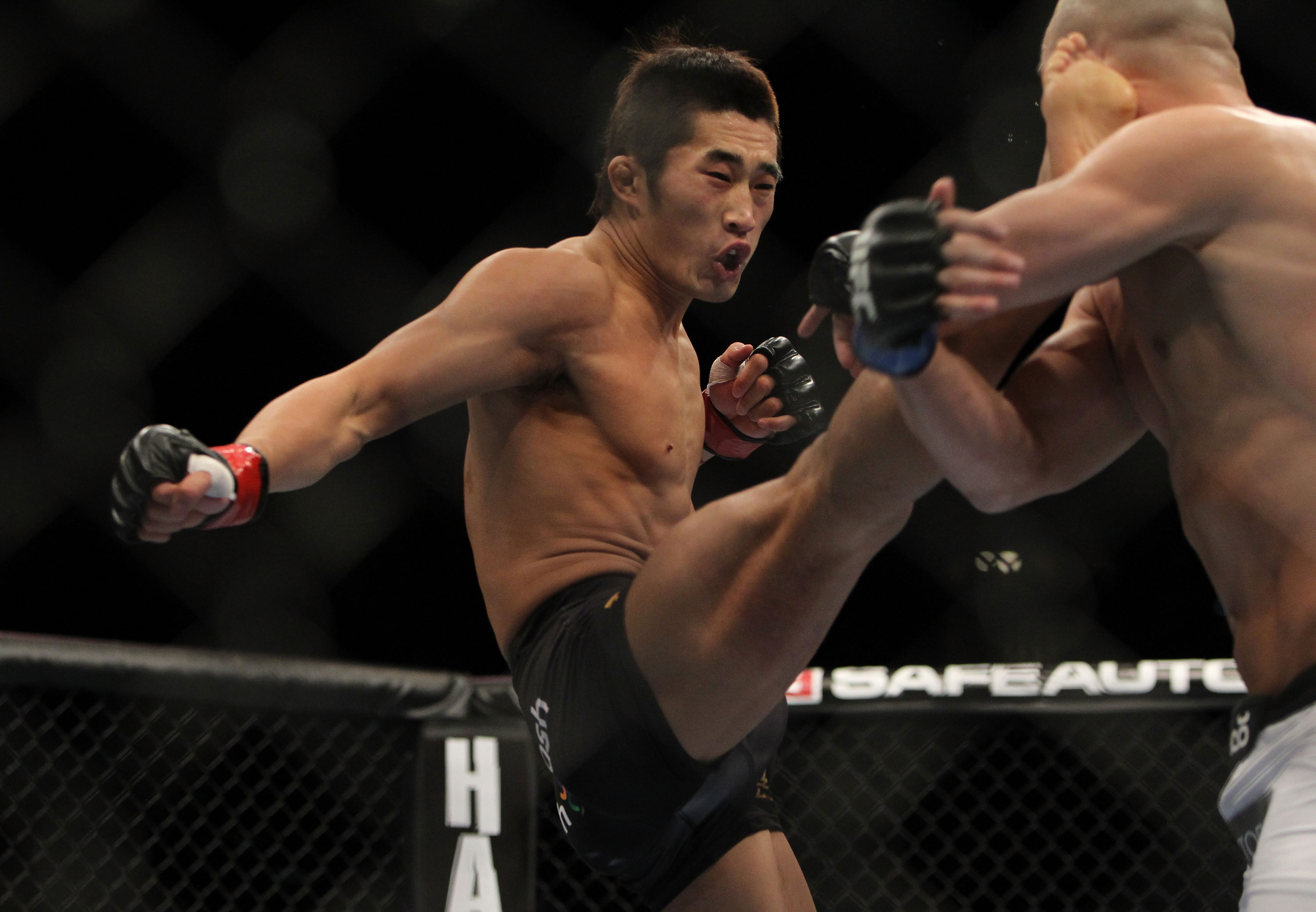 LAS VEGAS, NV - DECEMBER 30:  Dong Hyun Kim (black shorts) kicks Sean Pierson during the UFC 141 event at the MGM Grand Garden Arena on December 30, 2011 in Las Vegas, Nevada.  (Photo by Josh Hedges/Zuffa LLC/Zuffa LLC via Getty Images) *** Local Caption *** Dong Hyun Kim; Sean Pierson