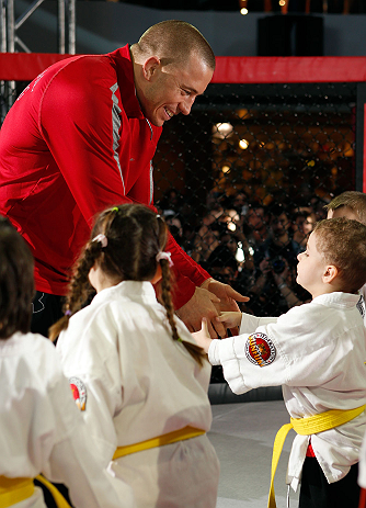 MONTREAL, QC - MARCH 13:  UFC welterweight champion Georges St-Pierre greets students of the Sunfuki Karate school during the UFC 158 open workouts at Complexe Desjardins on March 13, 2013 in Montreal, Quebec, Canada.  (Photo by Josh Hedges/Zuffa LLC/Zuffa LLC via Getty Images)