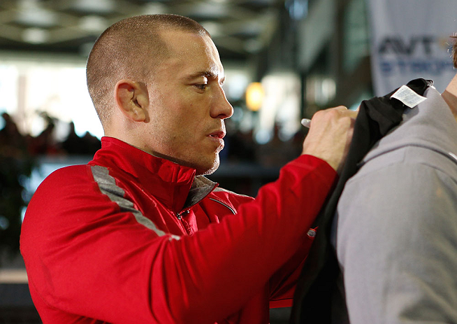 MONTREAL, QC - MARCH 13:  UFC welterweight champion Georges St-Pierre signs autographs for fans in attendance during the UFC 158 open workouts at Complexe Desjardins on March 13, 2013 in Montreal, Quebec, Canada.  (Photo by Josh Hedges/Zuffa LLC/Zuffa LLC via Getty Images)
