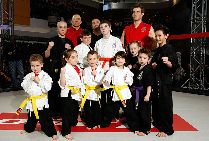 MONTREAL, QC - MARCH 13:  UFC welterweight champion Georges St-Pierre poses for photos with students of the Sunfuki Karate school during the UFC 158 open workouts at Complexe Desjardins on March 13, 2013 in Montreal, Quebec, Canada.  (Photo by Josh Hedges/Zuffa LLC/Zuffa LLC via Getty Images)
