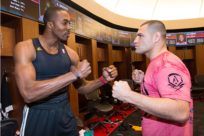 HOUSTON, TX - OCTOBER 16:  (R-L) UFC Heavyweight Champion Cain Velasquez and NBA Houston Rockets player Dwight Howard face off in the Houston Rockets locker room during the UFC 166 Ultimate Media Day at the Toyota Center on October 16, 2013 in Houston, Texas. (Photo by Jeff Bottari/Zuffa LLC/Zuffa LLC via Getty Images) *** Local Caption *** Cain Velasquez; Dwight Howard