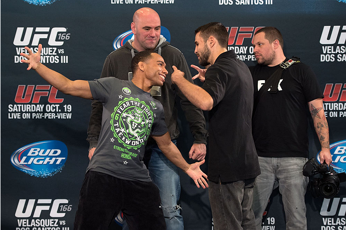 HOUSTON, TX - OCTOBER 16:  John Dodson (L) and Darrell Montague (R) face off in front of UFC President Dana White (C) for the media during the UFC 166 Ultimate Media Day at the Toyota Center on October 16, 2013 in Houston, Texas. (Photo by Jeff Bottari/Zuffa LLC/Zuffa LLC via Getty Images) *** Local Caption *** John Dodson; Darrell Montague; Dana White
