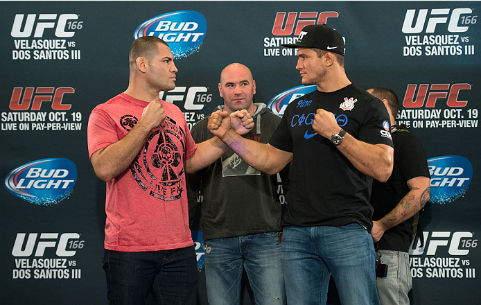 HOUSTON, TX - OCTOBER 16:  UFC Heavyweight Champion Cain Velasquez (L) and Junior Dos Santos (R) face off in front of UFC President Dana White (C) for the media during the UFC 166 Ultimate Media Day at the Toyota Center on October 16, 2013 in Houston, Texas. (Photo by Jeff Bottari/Zuffa LLC/Zuffa LLC via Getty Images) *** Local Caption *** Cain Velasquez; Junior Dos Santos; Dana White