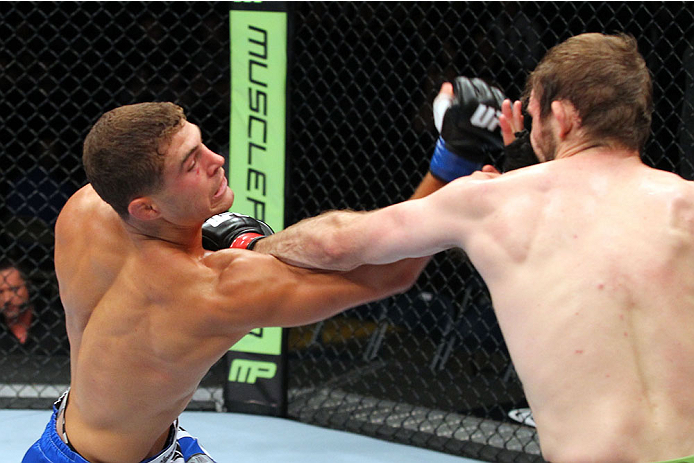 MILWAUKEE, WI - AUGUST 31:  (L-R) Al Iaquinta punches Ryan Couture in their UFC lightweight bout at BMO Harris Bradley Center on August 31, 2013 in Milwaukee, Wisconsin. (Photo by Ed Mulholland/Zuffa LLC/Zuffa LLC via Getty Images) *** Local Caption *** Ryan Couture; Al Iaquinta