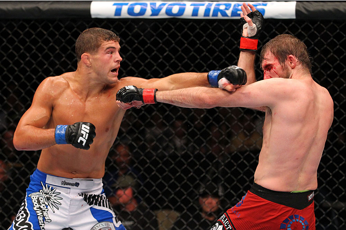 MILWAUKEE, WI - AUGUST 31:  (L-R) Al Iaquinta lands a punch against Ryan Couture in their UFC lightweight bout at BMO Harris Bradley Center on August 31, 2013 in Milwaukee, Wisconsin. (Photo by Ed Mulholland/Zuffa LLC/Zuffa LLC via Getty Images) *** Local Caption *** Ryan Couture; Al Iaquinta
