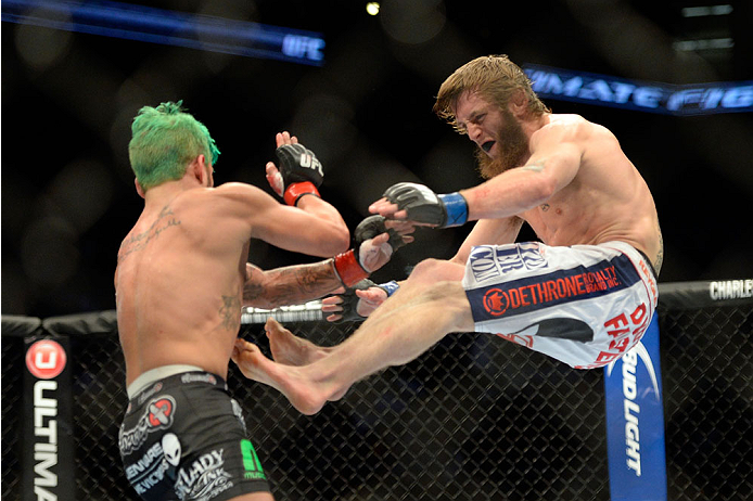 MILWAUKEE, WI - AUGUST 31:  (R-L) Tim Elliott jump kicks Louis Gaudinot in their UFC flyweight bout at BMO Harris Bradley Center on August 31, 2013 in Milwaukee, Wisconsin. (Photo by Jeff Bottari/Zuffa LLC/Zuffa LLC via Getty Images) *** Local Caption *** Louis Gaudinot; Tim Elliott