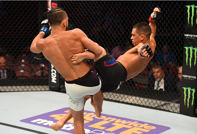 HOUSTON, TX - OCTOBER 03:  (R-L) Chris Cariaso is tripped after kicking Sergio Pettis in their flyweight bout during the UFC 192 event at the Toyota Center on October 3, 2015 in Houston, Texas. (Photo by Josh Hedges/Zuffa LLC/Zuffa LLC via Getty Images)