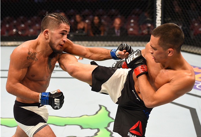 HOUSTON, TX - OCTOBER 03:  (R-L) Chris Cariaso kicks Sergio Pettis in their flyweight bout during the UFC 192 event at the Toyota Center on October 3, 2015 in Houston, Texas. (Photo by Josh Hedges/Zuffa LLC/Zuffa LLC via Getty Images)