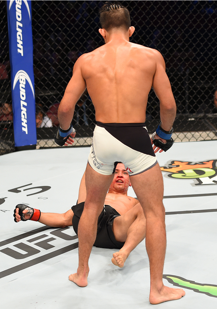 HOUSTON, TX - OCTOBER 03:  Chris Cariaso looks up at Sergio Pettis after being knocked down in their flyweight bout during the UFC 192 event at the Toyota Center on October 3, 2015 in Houston, Texas. (Photo by Josh Hedges/Zuffa LLC/Zuffa LLC via Getty Images)