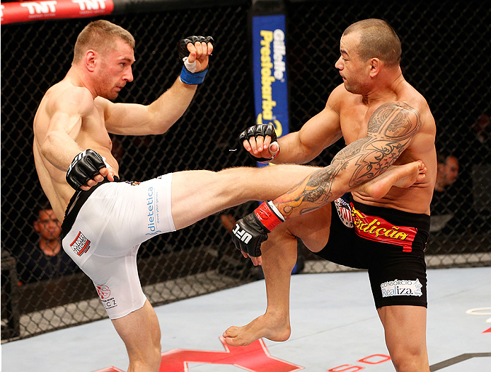 BRASILIA, BRAZIL - SEPTEMBER 13: (L-R) Piotr Hallmann of Poland kicks Gleison Tibau of Brazil in their lightweight bout during the UFC Fight Night event inside Nilson Nelson Gymnasium on September 13, 2014 in Brasilia, Brazil. (Photo by Josh Hedges/Zuffa LLC/Zuffa LLC via Getty Images)