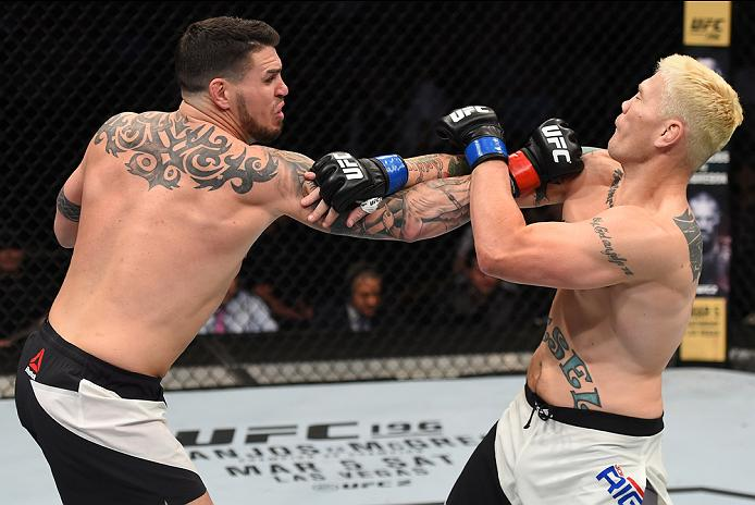 PITTSBURGH, PA - FEBRUARY 21:  (L-R) Chris Camozzi punches Joe Riggs in their middleweight bout during the UFC Fight Night event at Consol Energy Center on February 21, 2016 in Pittsburgh, Pennsylvania. (Photo by Jeff Bottari/Zuffa LLC/Zuffa LLC via Getty Images)