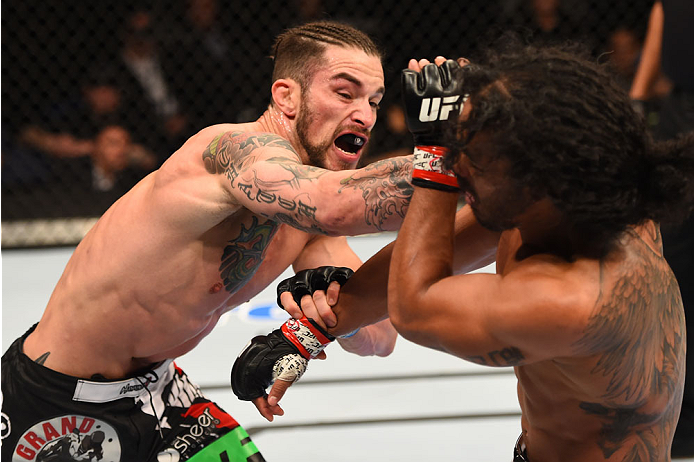 (L-R) Brandon Thatch punches Benson Henderson in their welterweight fight during the UFC Fight Night event inside 1stBank Center on 2/14/15 in Broomfield, CO. (Photo by Josh Hedges/Zuffa LLC)