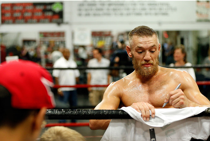 BOSTON, MA - AUGUST 13:  Irish featherweight Conor McGregor signs autographs for fans during an open training session for media at Peter Welch's Boxing Gym on August 13, 2013 in Boston, Massachusetts. (Photo by Josh Hedges/Zuffa LLC/Zuffa LLC via Getty Images)