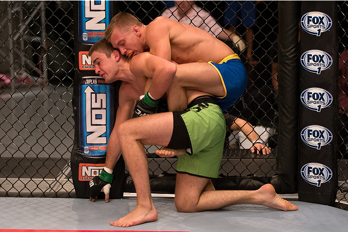 LAS VEGAS, NV - JUNE 19: Josh Hill (blue shorts) takes down Michael Wooten (green shorts) in their preliminary fight during filming of season eighteen of The Ultimate Fighter on June 19, 2013 in Las Vegas, Nevada. (Photo by Josh Hedges/Zuffa LLC/Zuffa LLC via Getty Images) *** Local Caption *** Michael Wooten; Josh Hill