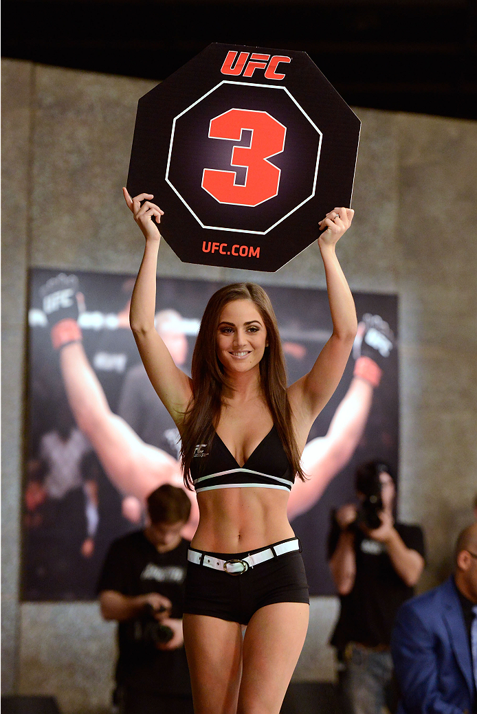 LACHUTE, CANADA - DECEMBER 2:  UFC Octagon Girl Stephanie Serfaty signals the start of round three between Team Australia fighter Vik Grujic and Team Canada fighter Luke Harris in their middleweight fight during filming of The Ultimate Fighter Nations television series on December 2, 2013 in Lachute, Quebec, Canada. (Photo by Richard Wolowicz/Zuffa LLC/Zuffa LLC via Getty Images) *** Local Caption *** Stephanie Serfaty