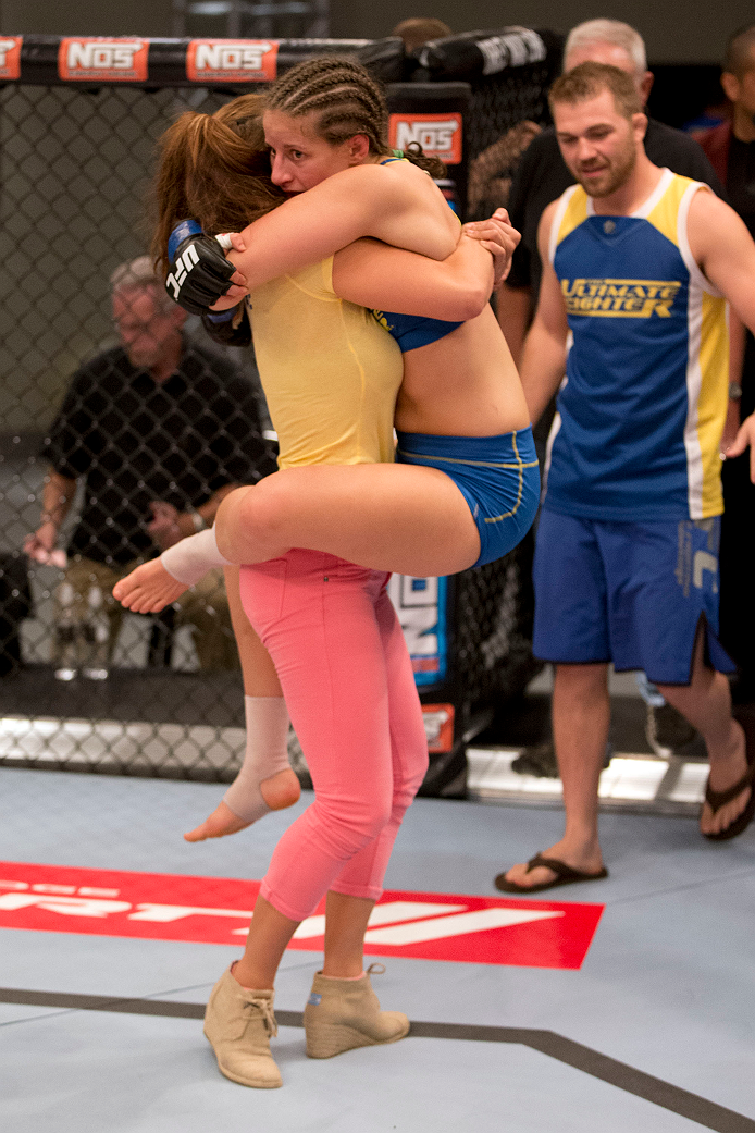 LAS VEGAS, NV - JUNE 21:  Sarah Moras (C) celebrates with her coach Miesha Tate (L) and trainer Brian Carraway (R) after winning her preliminary fight against Margaret Morgan (not pictured) during filming of season eighteen of The Ultimate Fighter on June 21, 2013 in Las Vegas, Nevada. (Photo by Josh Hedges/Zuffa LLC/Zuffa LLC via Getty Images) *** Local Caption *** Sarah Moras; Miesha Tate; Brian Carraway