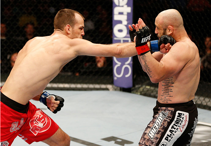 BOSTON, MA - AUGUST 17:  (L-R) Cole Miller punches Manny Gamburyan in their UFC featherweight bout at TD Garden on August 17, 2013 in Boston, Massachusetts. (Photo by Josh Hedges/Zuffa LLC/Zuffa LLC via Getty Images)