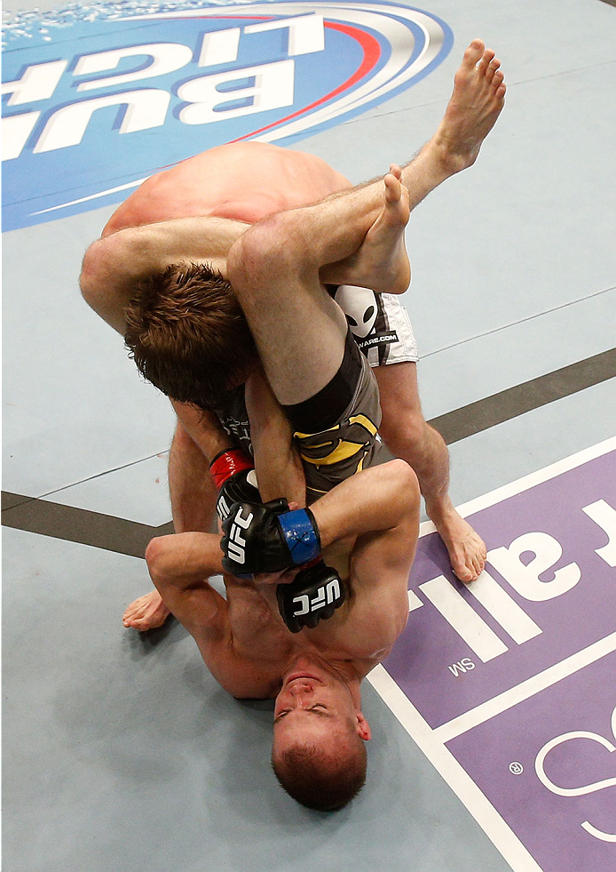 BOSTON, MA - AUGUST 17:  Michael McDonald (bottom) secures a triangle choke submission against Brad Pickett in their UFC bantamweight bout at TD Garden on August 17, 2013 in Boston, Massachusetts. (Photo by Josh Hedges/Zuffa LLC/Zuffa LLC via Getty Images)