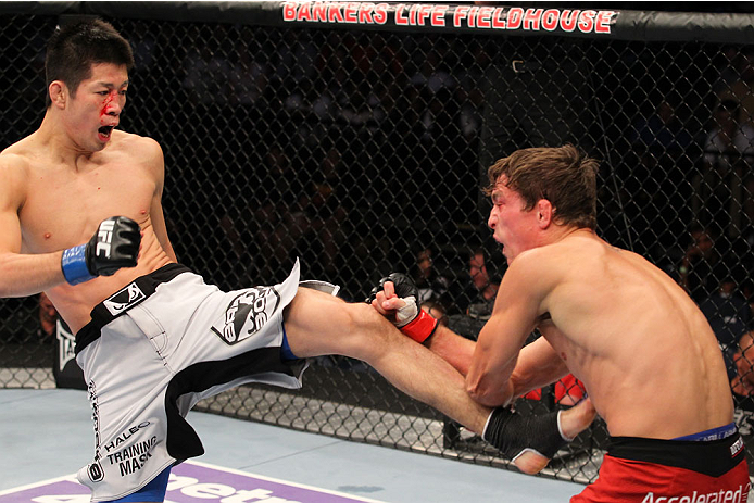 INDIANAPOLIS, IN - AUGUST 28:  (L-R) Hatsu Hioki kicks Darren Elkins in their featherweight fight during the UFC on FOX Sports 1 event at Bankers Life Fieldhouse on August 28, 2013 in Indianapolis, Indiana. (Photo by Ed Mulholland/Zuffa LLC/Zuffa LLC via Getty Images)