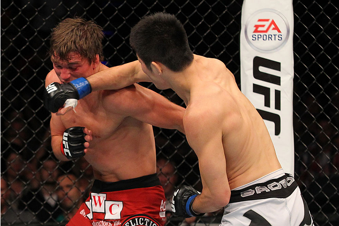 INDIANAPOLIS, IN - AUGUST 28:  (R-L) Hatsu Hioki punches Darren Elkins in their featherweight fight during the UFC on FOX Sports 1 event at Bankers Life Fieldhouse on August 28, 2013 in Indianapolis, Indiana. (Photo by Ed Mulholland/Zuffa LLC/Zuffa LLC via Getty Images)