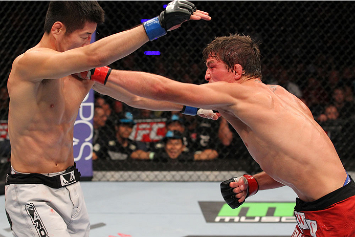 INDIANAPOLIS, IN - AUGUST 28:  (R-L) Darren Elkins punches Hatsu Hioki in their featherweight fight during the UFC on FOX Sports 1 event at Bankers Life Fieldhouse on August 28, 2013 in Indianapolis, Indiana. (Photo by Ed Mulholland/Zuffa LLC/Zuffa LLC via Getty Images)