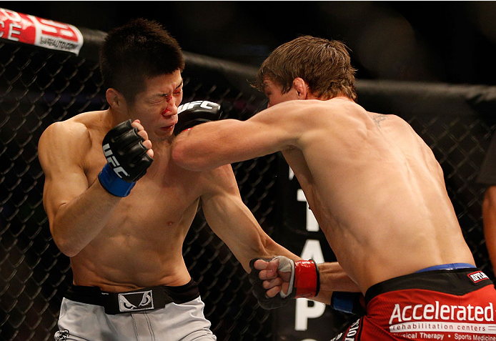 INDIANAPOLIS, IN - AUGUST 28:  (R-L) Darren Elkins punches Hatsu Hioki in their featherweight fight during the UFC on FOX Sports 1 event at Bankers Life Fieldhouse on August 28, 2013 in Indianapolis, Indiana. (Photo by Josh Hedges/Zuffa LLC/Zuffa LLC via Getty Images)