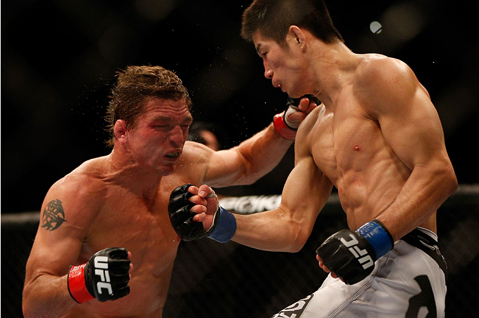 INDIANAPOLIS, IN - AUGUST 28:  (R-L) Hatsu Hioki punches Darren Elkins in their featherweight fight during the UFC on FOX Sports 1 event at Bankers Life Fieldhouse on August 28, 2013 in Indianapolis, Indiana. (Photo by Josh Hedges/Zuffa LLC/Zuffa LLC via Getty Images)