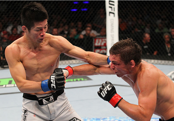 INDIANAPOLIS, IN - AUGUST 28:  (L-R) Hatsu Hioki and Darren Elkins trade punches in their featherweight fight during the UFC on FOX Sports 1 event at Bankers Life Fieldhouse on August 28, 2013 in Indianapolis, Indiana. (Photo by Ed Mulholland/Zuffa LLC/Zuffa LLC via Getty Images)