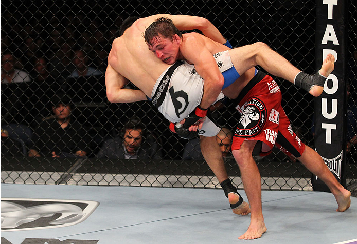 INDIANAPOLIS, IN - AUGUST 28:  (R-L) Darren Elkins takes down Hatsu Hioki in their featherweight fight during the UFC on FOX Sports 1 event at Bankers Life Fieldhouse on August 28, 2013 in Indianapolis, Indiana. (Photo by Ed Mulholland/Zuffa LLC/Zuffa LLC via Getty Images)