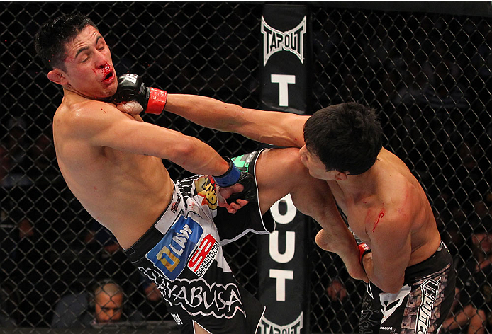 INDIANAPOLIS, IN - AUGUST 28:  (R-L) Takeya Mizugaki punches Erik Perez in their bantamweight fight during the UFC on FOX Sports 1 event at Bankers Life Fieldhouse on August 28, 2013 in Indianapolis, Indiana. (Photo by Ed Mulholland/Zuffa LLC/Zuffa LLC via Getty Images)