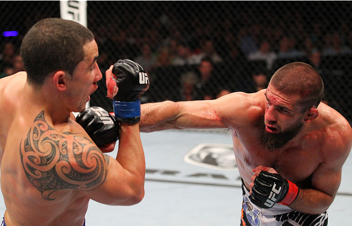 INDIANAPOLIS, IN - AUGUST 28:  (R-L) Court McGee punches Robert Whittaker in their welterweight fight during the UFC on FOX Sports 1 event at Bankers Life Fieldhouse on August 28, 2013 in Indianapolis, Indiana. (Photo by Ed Mulholland/Zuffa LLC/Zuffa LLC via Getty Images)