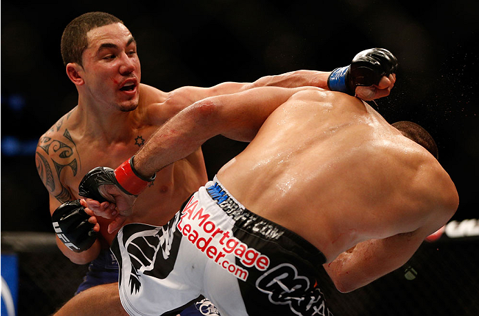 INDIANAPOLIS, IN - AUGUST 28:  (R-L) Robert Whittaker punches Court McGee in their welterweight fight during the UFC on FOX Sports 1 event at Bankers Life Fieldhouse on August 28, 2013 in Indianapolis, Indiana. (Photo by Josh Hedges/Zuffa LLC/Zuffa LLC via Getty Images)