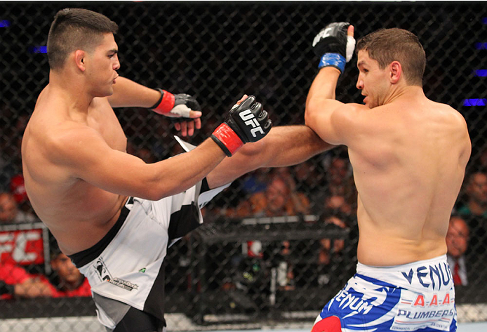 INDIANAPOLIS, IN - AUGUST 28:  (L-R) Kelvin Gastelum kicks Brian Melancon in their welterweight fight during the UFC on FOX Sports 1 event at Bankers Life Fieldhouse on August 28, 2013 in Indianapolis, Indiana. (Photo by Ed Mulholland/Zuffa LLC/Zuffa LLC via Getty Images)