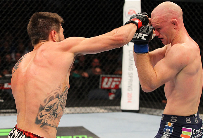 INDIANAPOLIS, IN - AUGUST 28:  (L-R) Carlos Condit punches Martin Kampmann in their welterweight fight during the UFC on FOX Sports 1 event at Bankers Life Fieldhouse on August 28, 2013 in Indianapolis, Indiana. (Photo by Ed Mulholland/Zuffa LLC/Zuffa LLC via Getty Images)