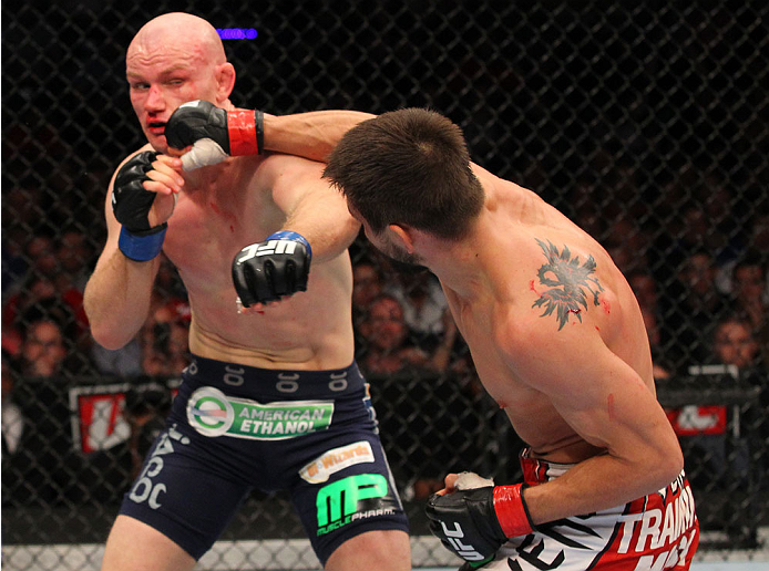 INDIANAPOLIS, IN - AUGUST 28:  (R-L) Carlos Condit punches Martin Kampmann in their welterweight fight during the UFC on FOX Sports 1 event at Bankers Life Fieldhouse on August 28, 2013 in Indianapolis, Indiana. (Photo by Ed Mulholland/Zuffa LLC/Zuffa LLC via Getty Images)