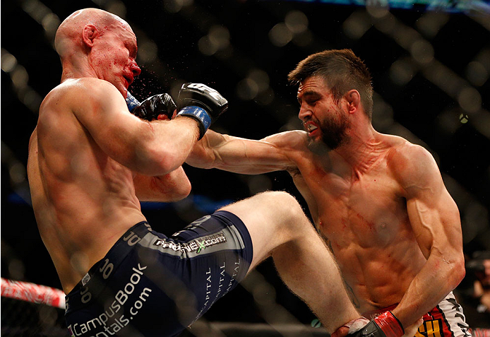 INDIANAPOLIS, IN - AUGUST 28:  (R-L) Carlos Condit punches Martin Kampmann in their welterweight fight during the UFC on FOX Sports 1 event at Bankers Life Fieldhouse on August 28, 2013 in Indianapolis, Indiana. (Photo by Josh Hedges/Zuffa LLC/Zuffa LLC via Getty Images)