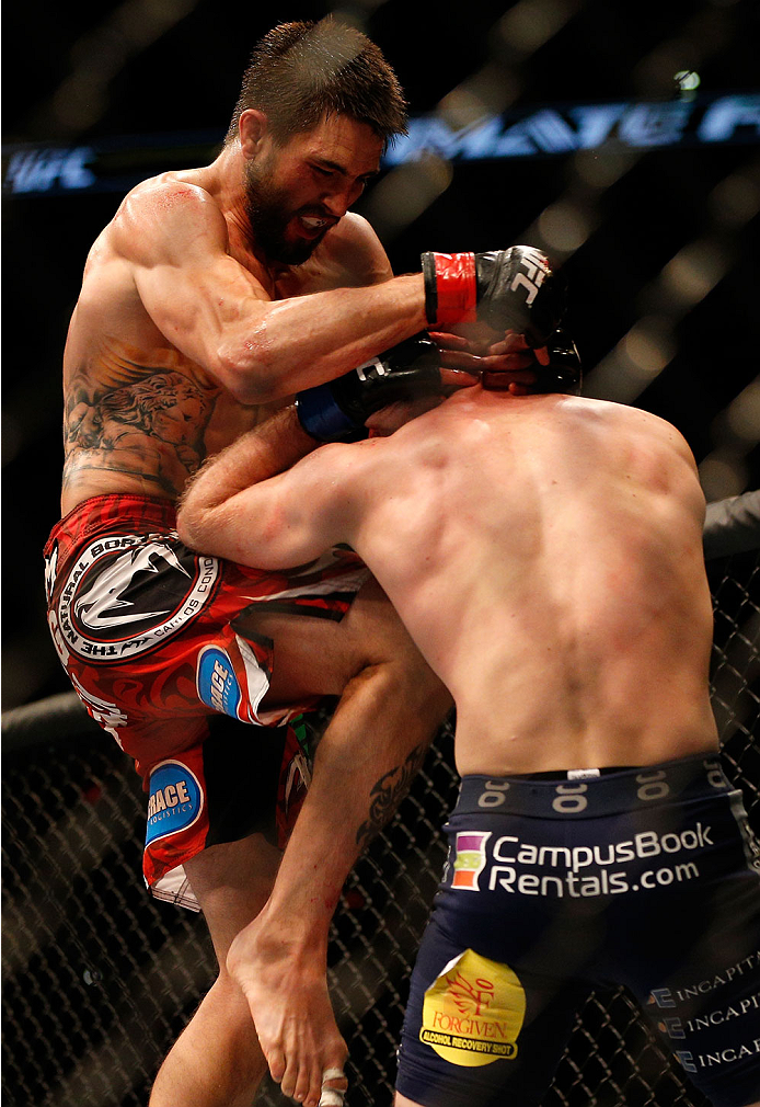 INDIANAPOLIS, IN - AUGUST 28:  (L-R) Carlos Condit knees Martin Kampmann in their welterweight fight during the UFC on FOX Sports 1 event at Bankers Life Fieldhouse on August 28, 2013 in Indianapolis, Indiana. (Photo by Josh Hedges/Zuffa LLC/Zuffa LLC via Getty Images)