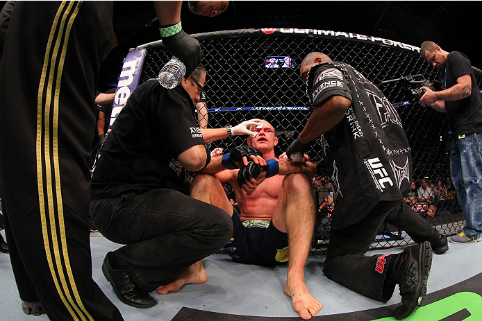 INDIANAPOLIS, IN - AUGUST 28:  Martin Kampmann is treated by cut men after his TKO loss to Carlos Condit in their welterweight fight during the UFC on FOX Sports 1 event at Bankers Life Fieldhouse on August 28, 2013 in Indianapolis, Indiana. (Photo by Ed Mulholland/Zuffa LLC/Zuffa LLC via Getty Images)