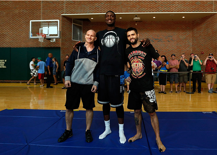 INDIANAPOLIS, IN - AUGUST 26:  Opponents Martin Kampmann (L) and Carlos Condit (R) pose for photos with Indiana Pacers center Roy Hibbert at Banker's Life Fieldhouse on August 26, 2013 in Indianapolis, Indiana. (Photo by Josh Hedges/Zuffa LLC/Zuffa LLC via Getty Images)