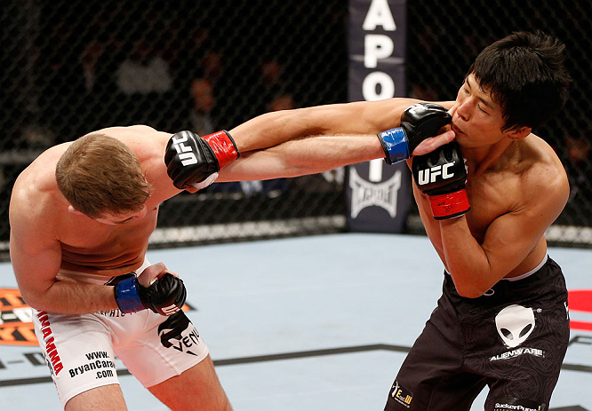 SAITAMA, JAPAN - MARCH 03:  (R-L) Takeya Mizugaki and Bryan Caraway trade punches in their bantamweight fight during the UFC on FUEL TV event at Saitama Super Arena on March 3, 2013 in Saitama, Japan.  (Photo by Josh Hedges/Zuffa LLC/Zuffa LLC via Getty Images)