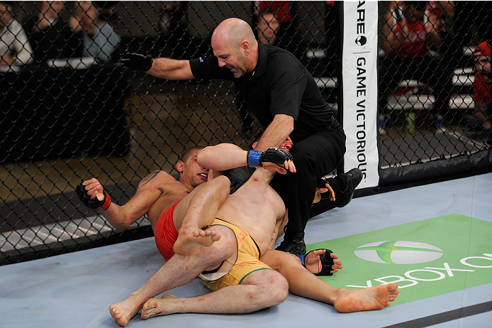 LACHUTE, CANADA - NOVEMBER 2:  Referee Yves Lavigne (black shirt) stops the fight between Team Canada fighter Kajan Johnson (red shorts) and Team Australia fighter Brendan O'Reilly (green shorts) after Johnson submitted O'Reilly in their welterweight bout during filming of The Ultimate Fighter Nations television series on November 2, 2013 in Lachute, Quebec, Canada. (Photo by Richard Wolowicz/Zuffa LLC/Zuffa LLC via Getty Images) *** Local Caption *** Brendan O'Reilly; Kajan Johnson; Yves Lavigne
