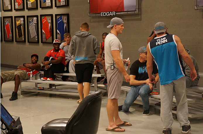 Coach Mark Coleman talks with members of Team Penn before the final quarterfinal bout begins.