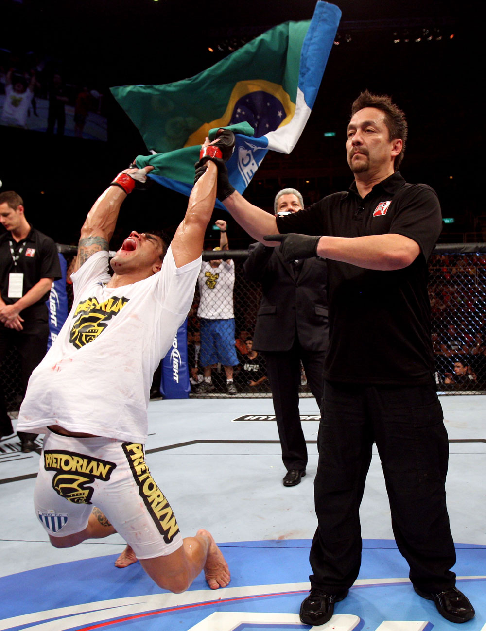 RIO DE JANEIRO, BRAZIL - JANUARY 14:  Referee Mario Yamasaki (R) holds up Thiago Tavares (L) hand as he celebrates after defeating Sam Stout (not pictured) in a lightweight bout during UFC 142 at HSBC Arena on January 14, 2012 in Rio de Janeiro, Brazil.  (Photo by Josh Hedges/Zuffa LLC/Zuffa LLC via Getty Images)