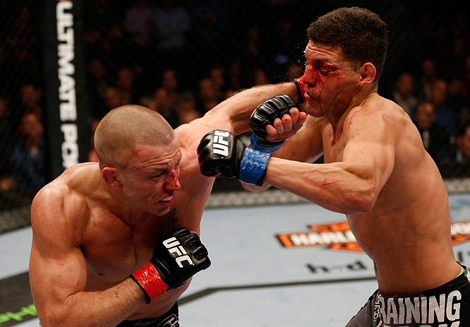 MONTREAL, QC - MARCH 16:  (L-R) Georges St-Pierre punches Nick Diaz in their welterweight championship bout during the UFC 158 event at Bell Centre on March 16, 2013 in Montreal, Quebec, Canada.  (Photo by Josh Hedges/Zuffa LLC/Zuffa LLC via Getty Images)