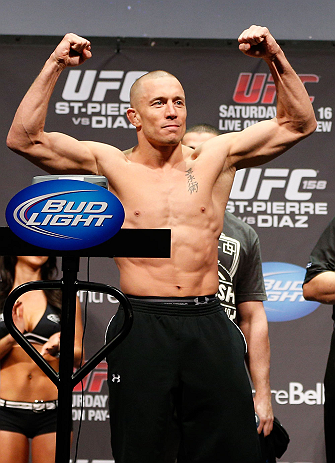 MONTREAL, QC - MARCH 15:  Georges St-Pierre raises his arms during the UFC 158 weigh-in at Bell Centre on March 15, 2013 in Montreal, Quebec, Canada.  (Photo by Josh Hedges/Zuffa LLC/Zuffa LLC via Getty Images)