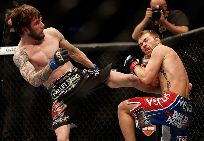 NEWARK, NJ - APRIL 27:   (L-R) Johny Bedford kicks Bryan Caraway in their bantamweight fight during the UFC 159 event at the Prudential Center on April 27, 2013 in Newark, New Jersey.  (Photo by Josh Hedges/Zuffa LLC/Zuffa LLC via Getty Images)