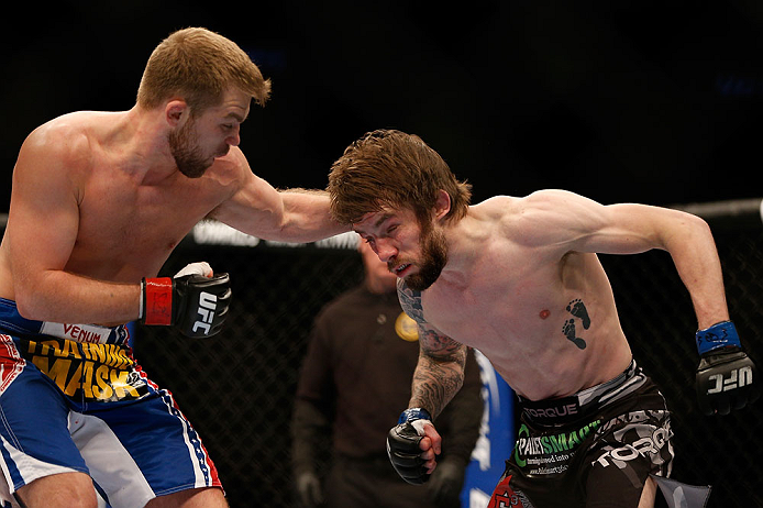 NEWARK, NJ - APRIL 27:   (L-R) Bryan Caraway punches Johny Bedford in their bantamweight fight during the UFC 159 event at the Prudential Center on April 27, 2013 in Newark, New Jersey.  (Photo by Josh Hedges/Zuffa LLC/Zuffa LLC via Getty Images)