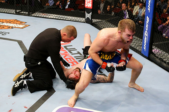NEWARK, NJ - APRIL 27:  Bryan Caraway (R) celebrates winning by submission (guillotine choke) against Johnny Bedford (C) in their bantamweight bout during the UFC 159 event at the Prudential Center on April 27, 2013 in Newark, New Jersey.  (Photo by Al Bello/Zuffa LLC/Zuffa LLC Via Getty Images)